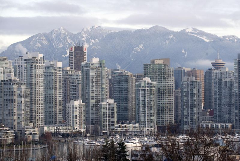 Photo shows Vancouver skyline with high-rise condos in foreground and mountains in background.